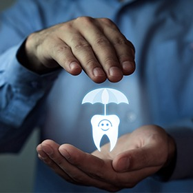 Hands holding an animated tooth under an umbrella