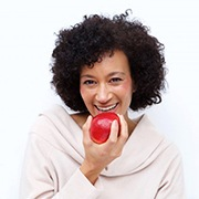 woman biting into a red apple
