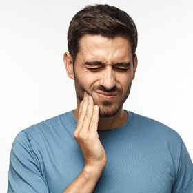 Man in grey with tooth pain