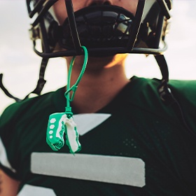 Football player with green mouthguard hanging from helmet