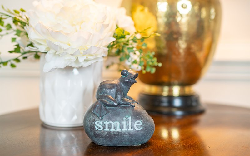 Small stone statuette that says smile