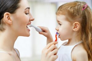 A woman and young girl brushing each other's teeth.