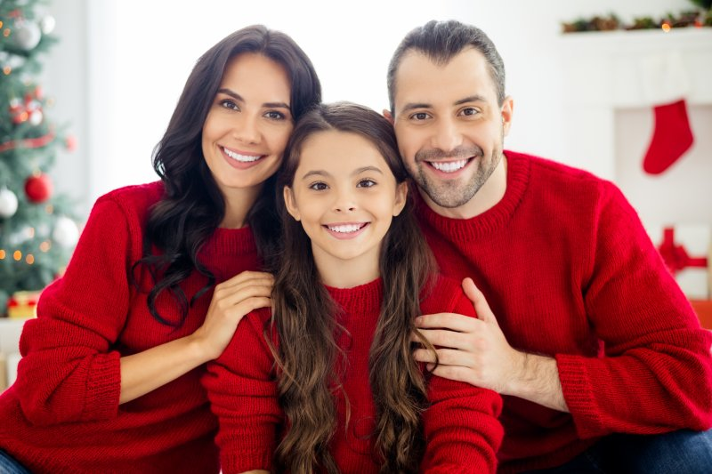 a family in red sweaters smiling