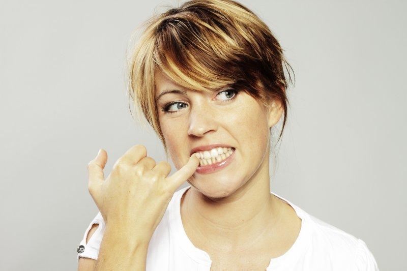 woman picking something in between her teeth